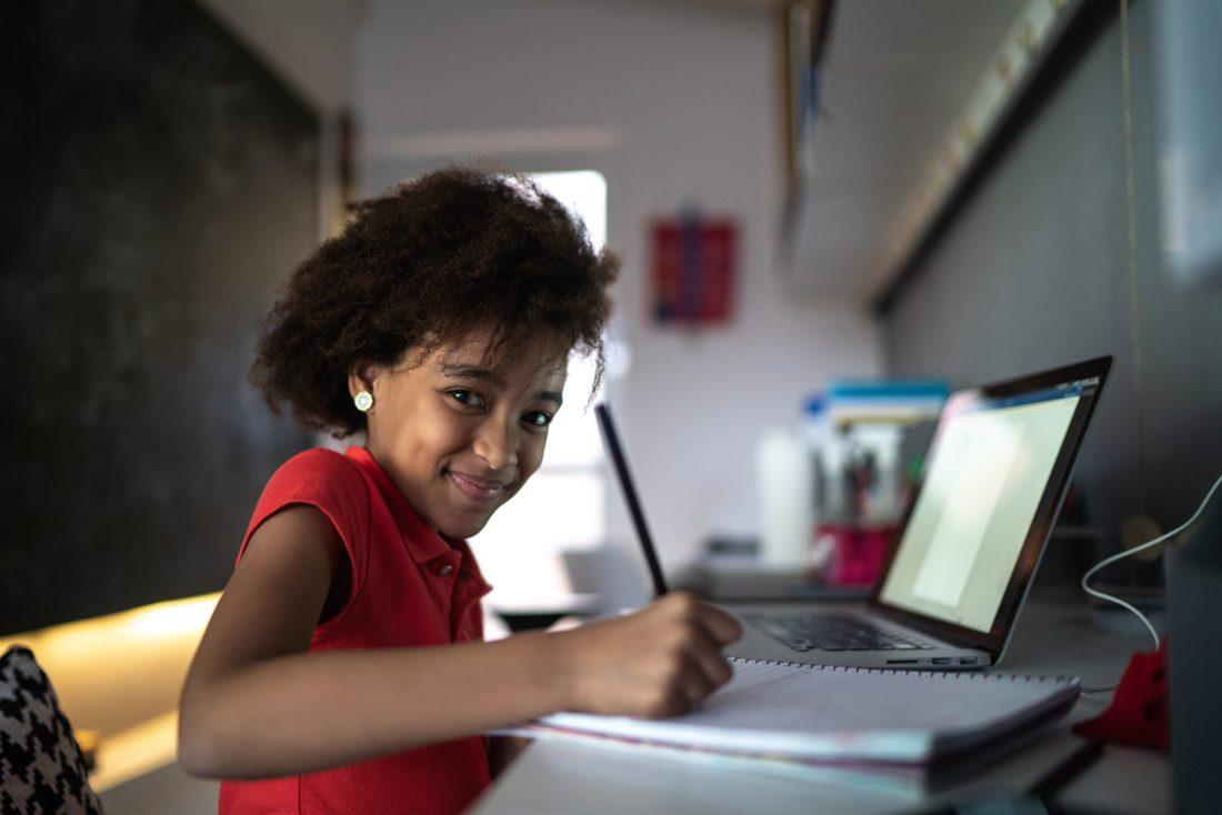 Na imagem aparece uma menina sorrindo com lápis na mão, em sua rotina de estudos em casa