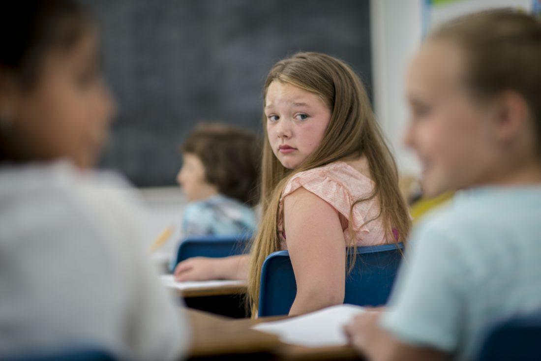 Menina em sala de aula observando a conversa de outros colegas