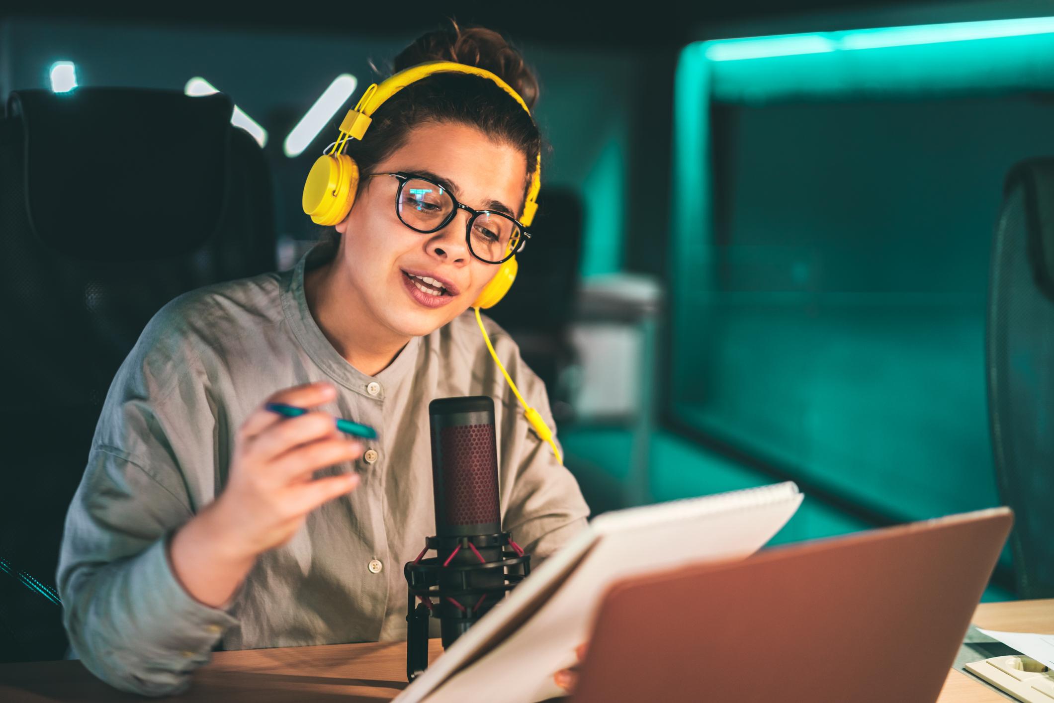 Estudante com fone de ouvido, microfone e caderno na mão, gravando podcast
