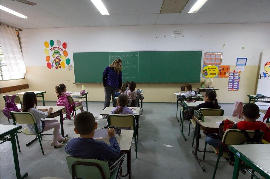 Na foto, alunos estão em uma sala de aula acompanhados de uma professora