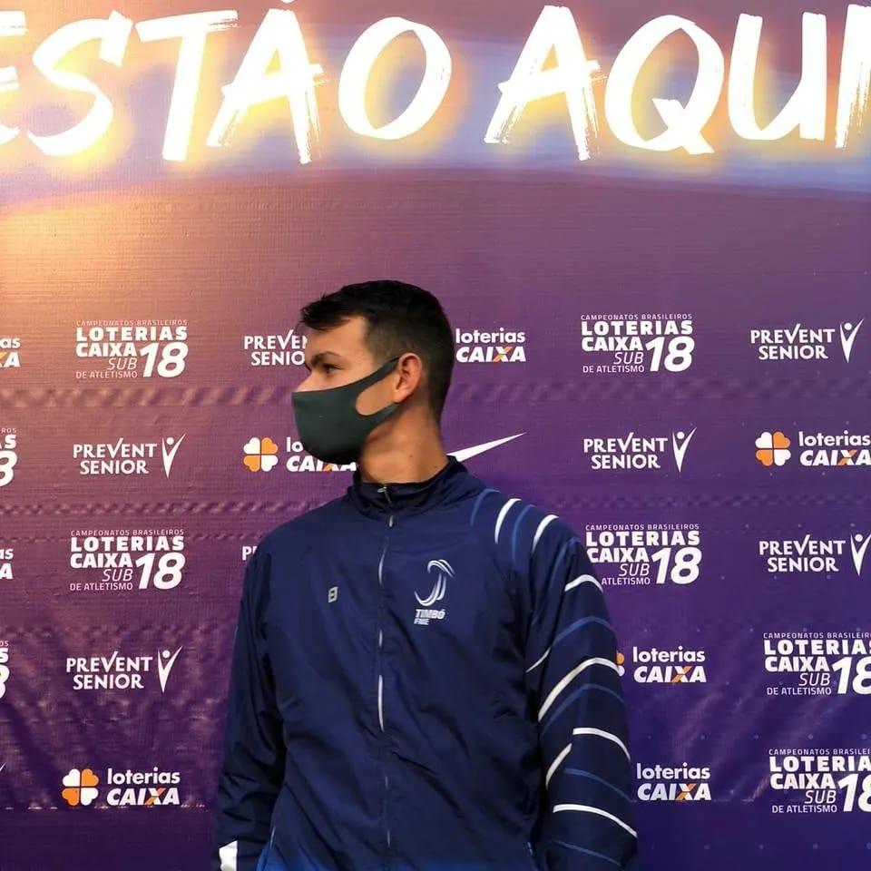 Atleta em pé, usando máscara, na frente de uma parede com o slogan do Campeonato Brasileiro Loterias Caixa de Atletismo Sub-18