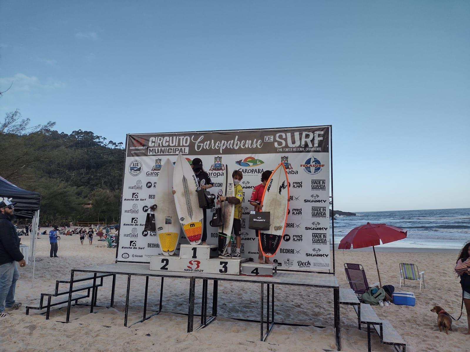 Surfistas em cima de um pódio, recebendo a premiação de um campeonato de surfe na Praia da Ferrugem em Garopaba