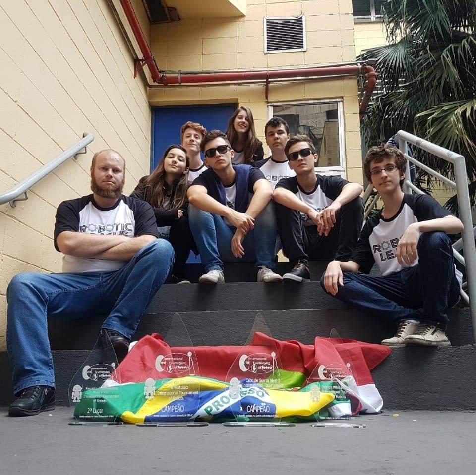 Alunos da oficina de robótica e astronáutica do professor Carlos Rutz sentados na escada com a bandeira do Brasil e do estado de Santa Catarina e troféu internacional do International Tournment of Robots em 2018