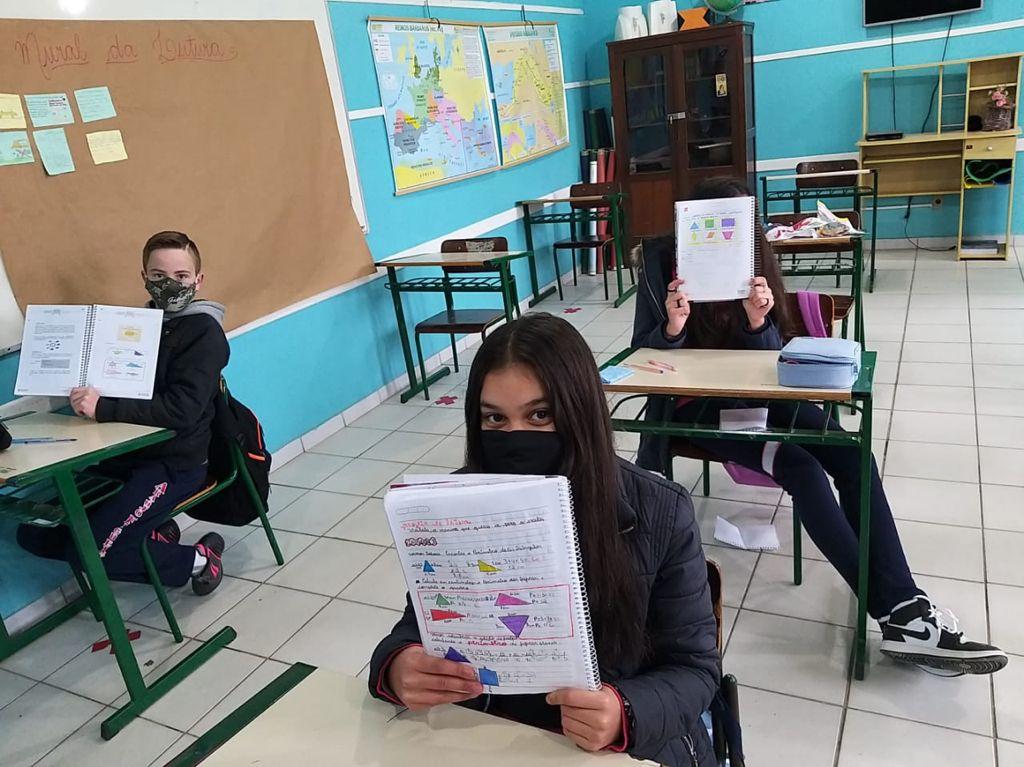 "Estudantes em sala de aula na EEB Araújo Figueiredo, de Urubici, segurando caderno e aprendendo matemática no projeto escolar ""Malala"""