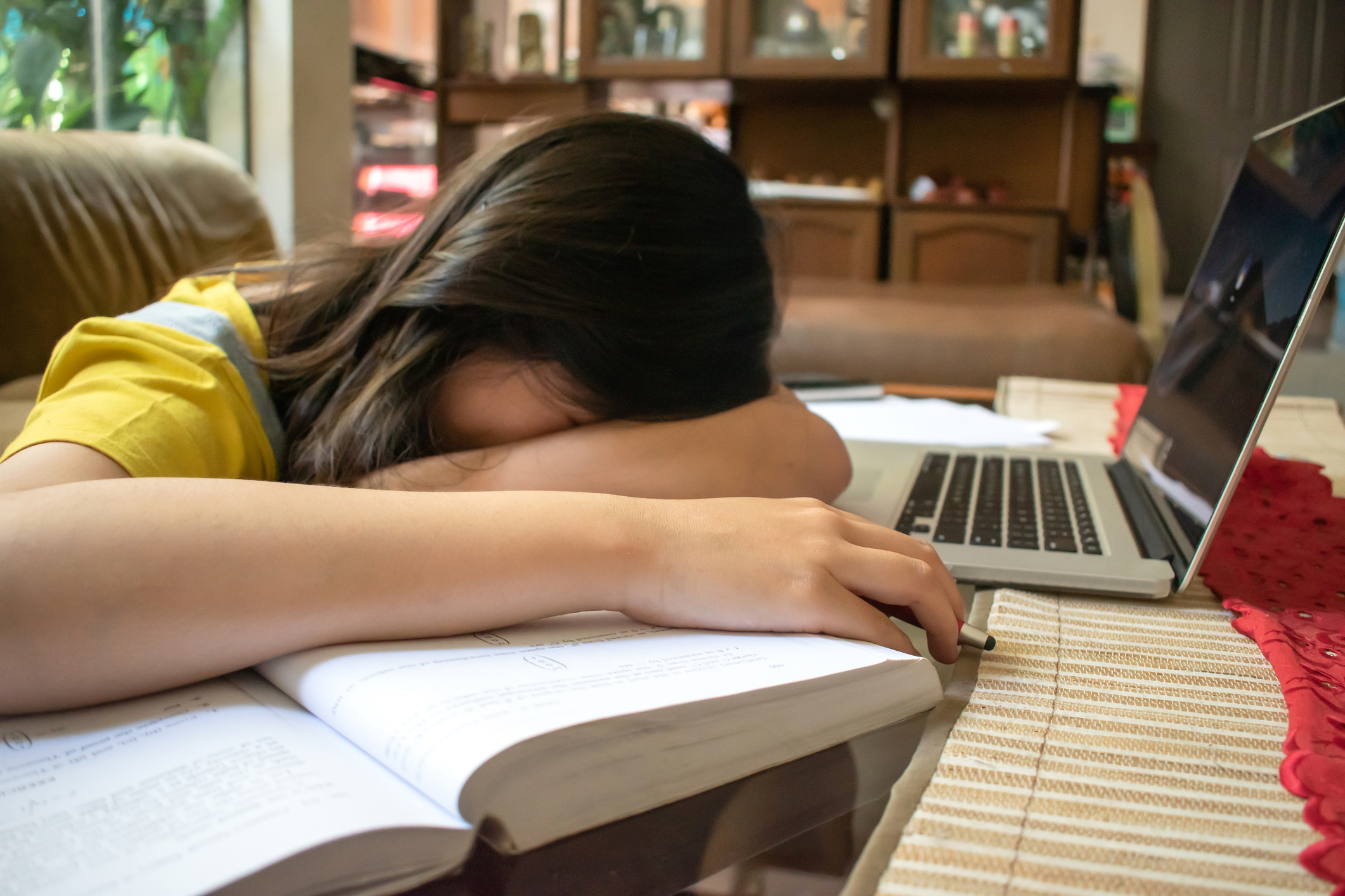 Na imagem, uma menina com a cabeça deitada nos livros e com sono