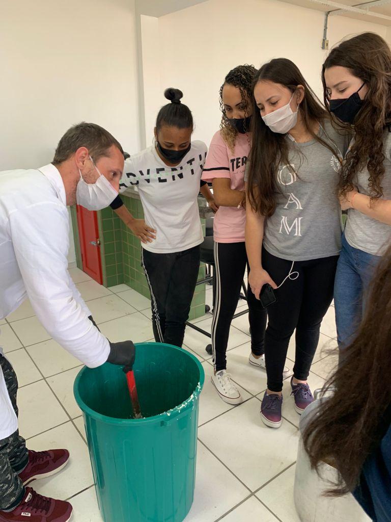 Alunos no laboratório de química da EEB Professora Gracinda Augusta Machado, de Imbituba, sendo orientados por professor de química, na produção de itens de higirn